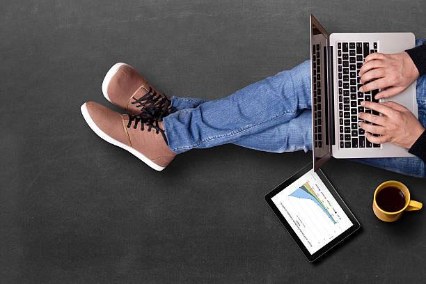 Pessoa utilizando notebook e tablet para estudar